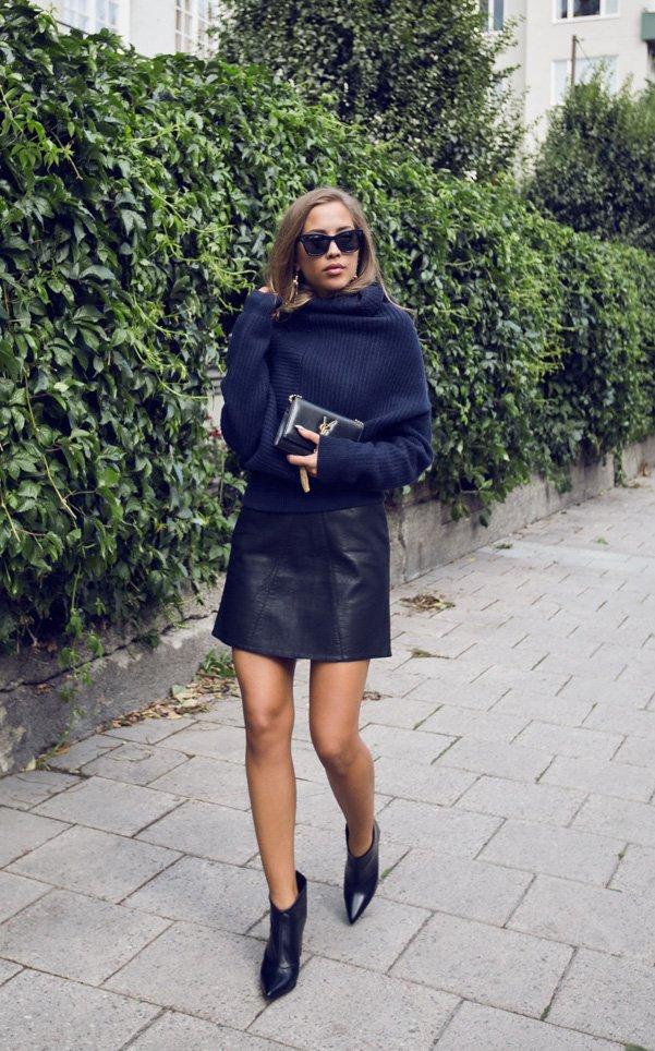 На фото: короткая черная кожаная юбка яркое сочетание с темным верхом.