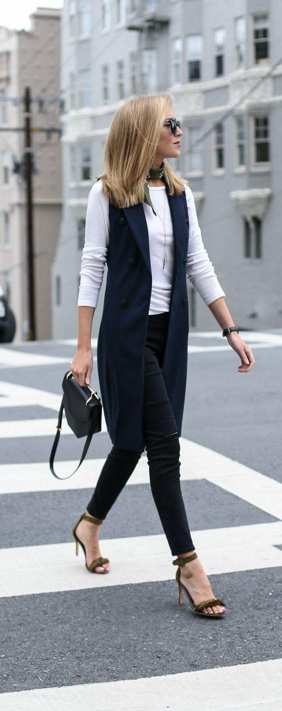 На фото: длинный жилет черного цвета в сочетании с черными брюками и кофтой белого цвета.