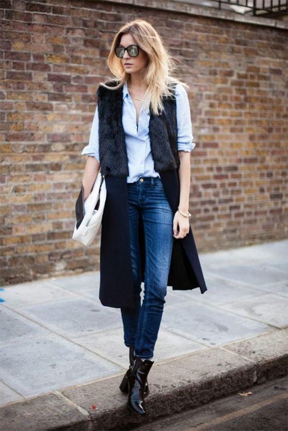 На фото: длинный жилет черного цвета в сочетании с черными брюками и кофтой голубого цвета.
