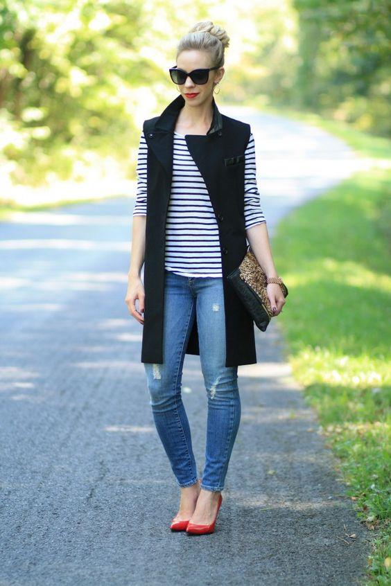 На фото: длинный жилет чернрго цвета в сочетании в джинсами и кофтой в полоску.