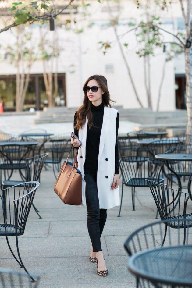 На фото: длинный жилет белого цвета в сочетании с черными брюками и кофтой черного цвета.
