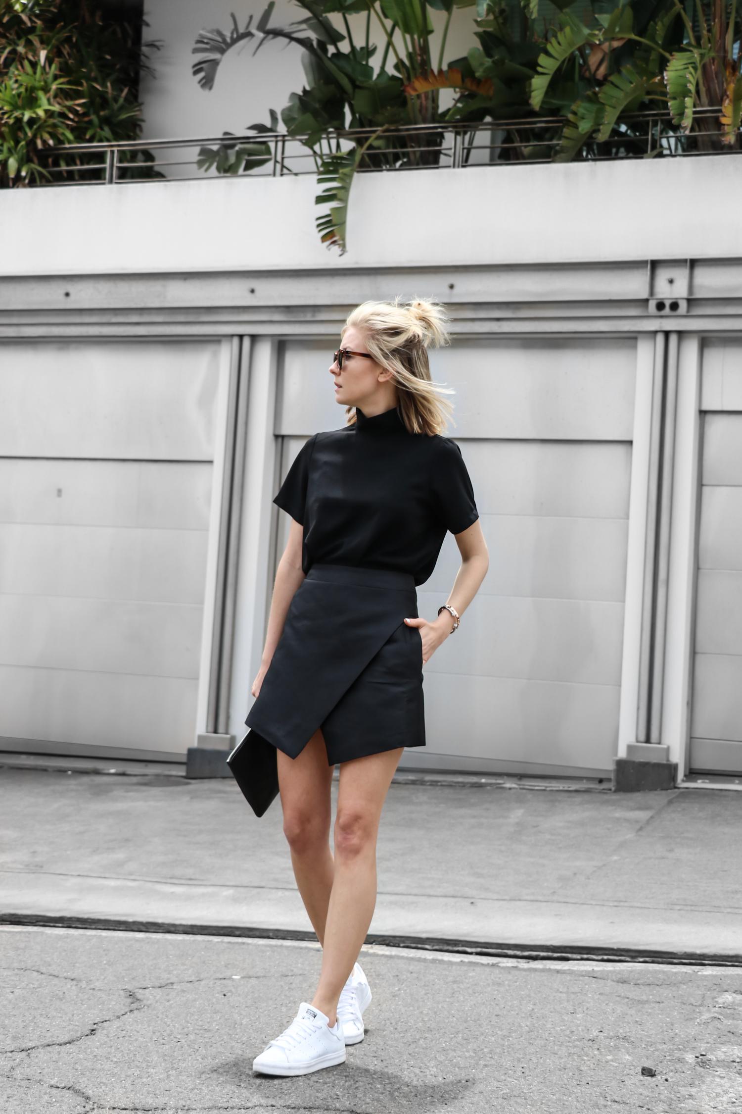 На фото: белые кроссовки с черной короткой юбкой.
