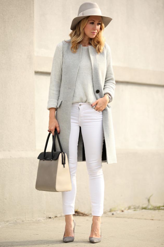 На фото: длинный жилет серого цвета в сочетании с белыми брюками и кофтой светло серого цвета.