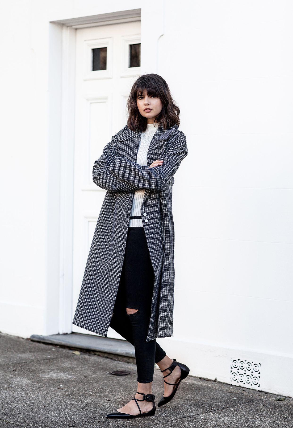 На фото: длинное пальто в клетку: новое красивое сочетание с белой кофтой , черными рваными джинсами и черными туфлями.