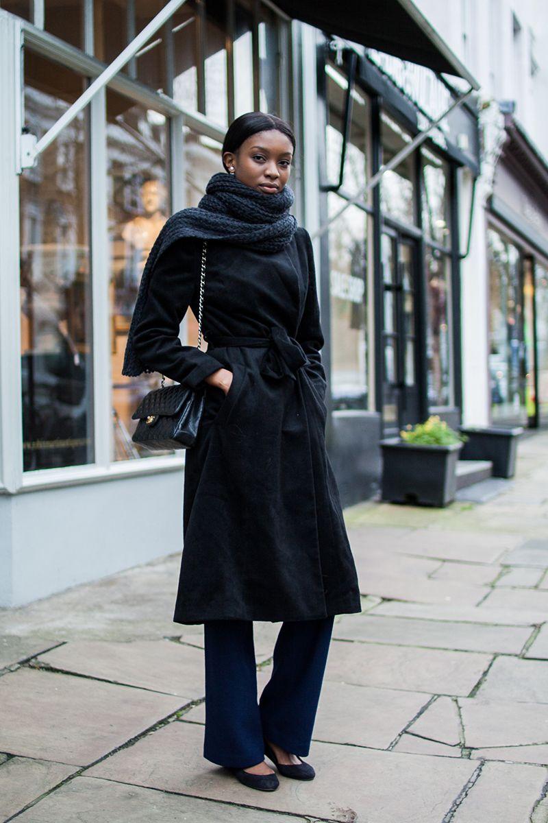 На фото: длинное черное пальто: новое красивое сочетаниес черными расклешенными брюками.