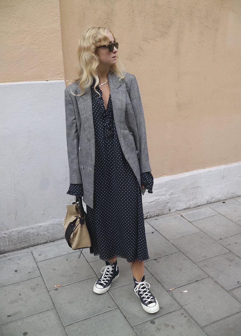 На фото: новый крутой лук на каждый день - серый удлиненный пиджак счерным платьем в горошек и кедами.