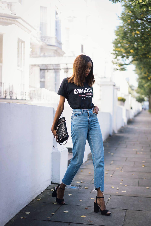 На фото: новый крутой лук на каждый день - черная футболка с принтом с джинсами.