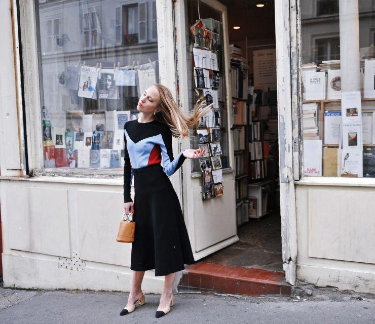 На фото: новый крутой лук на каждый день - блузка черная с голубым цветом с расклешонной черной юбкой и черно бежевыми туфлями.