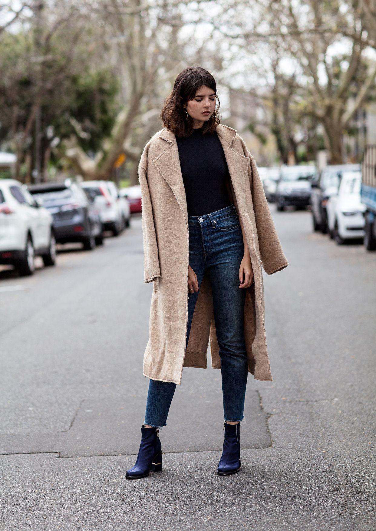 На фото: новый крутой лук на каждый день - бежевое пальто с черной блузкой и укороченными брюками и черными ботильонами.
