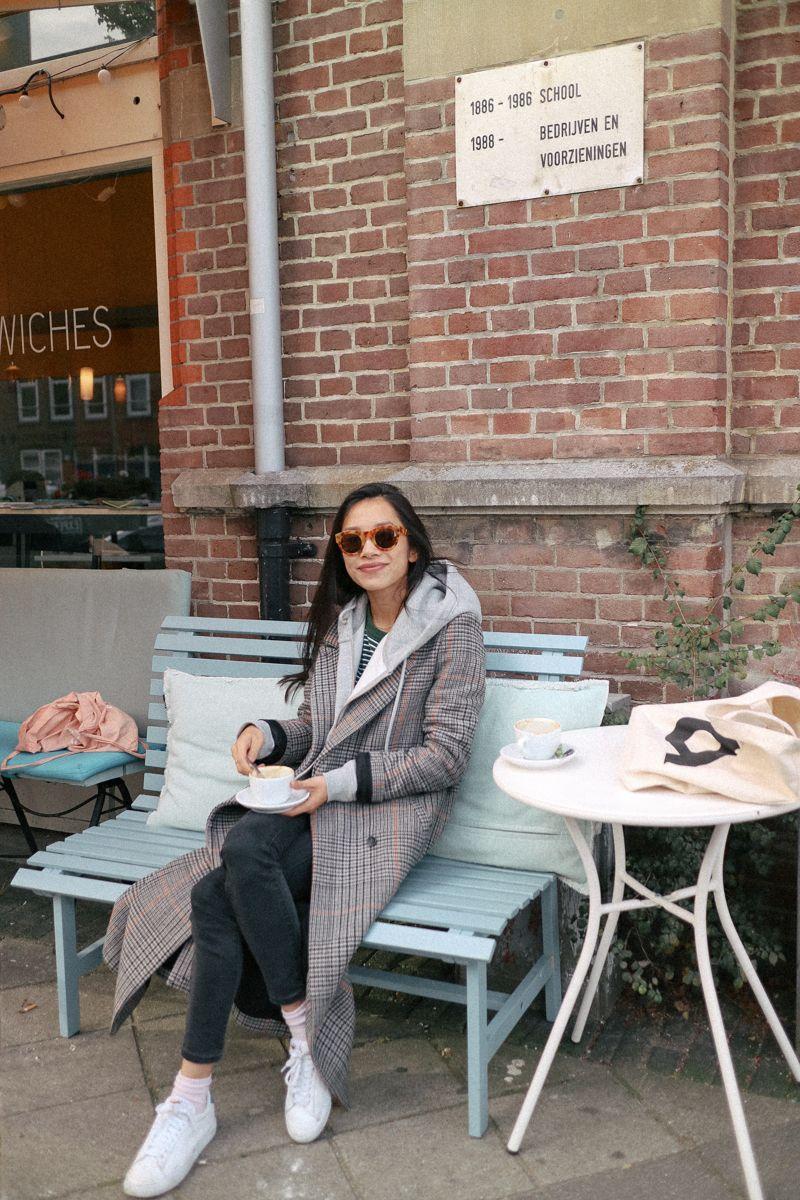 На фото: новый крутой лук на каждый день - клетчатое пальто с капюшоном черными узкимиджинсами и белыми туфлями.