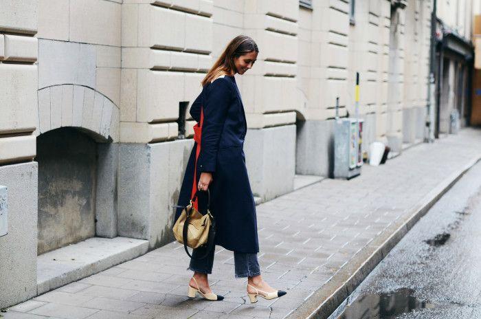 На фото: новый крутой лук на каждый день - черный плащ с укороченными расклешоными джинсами и черно бежевыми босоножками.