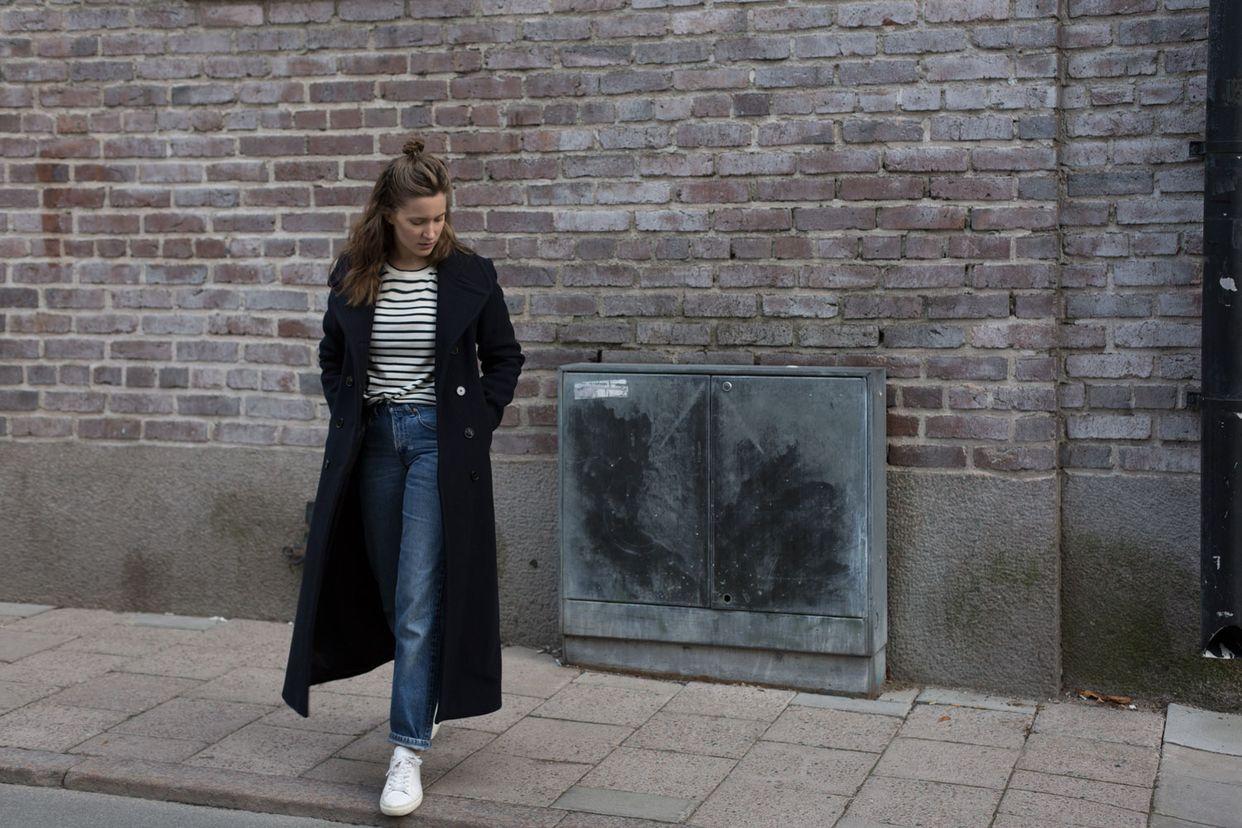 На фото: новый крутой лук на каждый день - черное длинное пальто сджинсами и белыми туфлями.