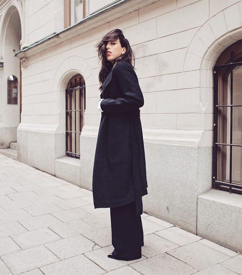 На фото: новый стильный образ - черное пальто оверсайз с узкими черными расклешонными брюками.