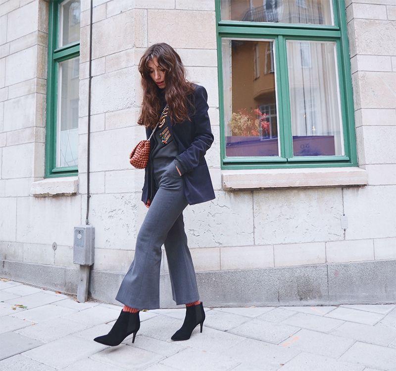 На фото: новый стильный образ - черная куртка с расклешенными укороченными джинсами.