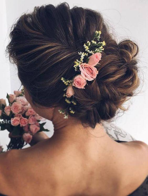 Романтичная прическа 2017 года с косой, собранной в пучок, и украшенной нежными цветами