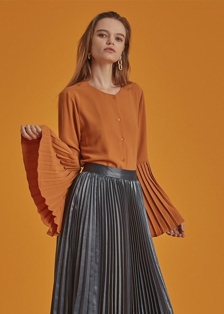 На фото: оранжевая блузка с расклешенными рофрированными рукавами.