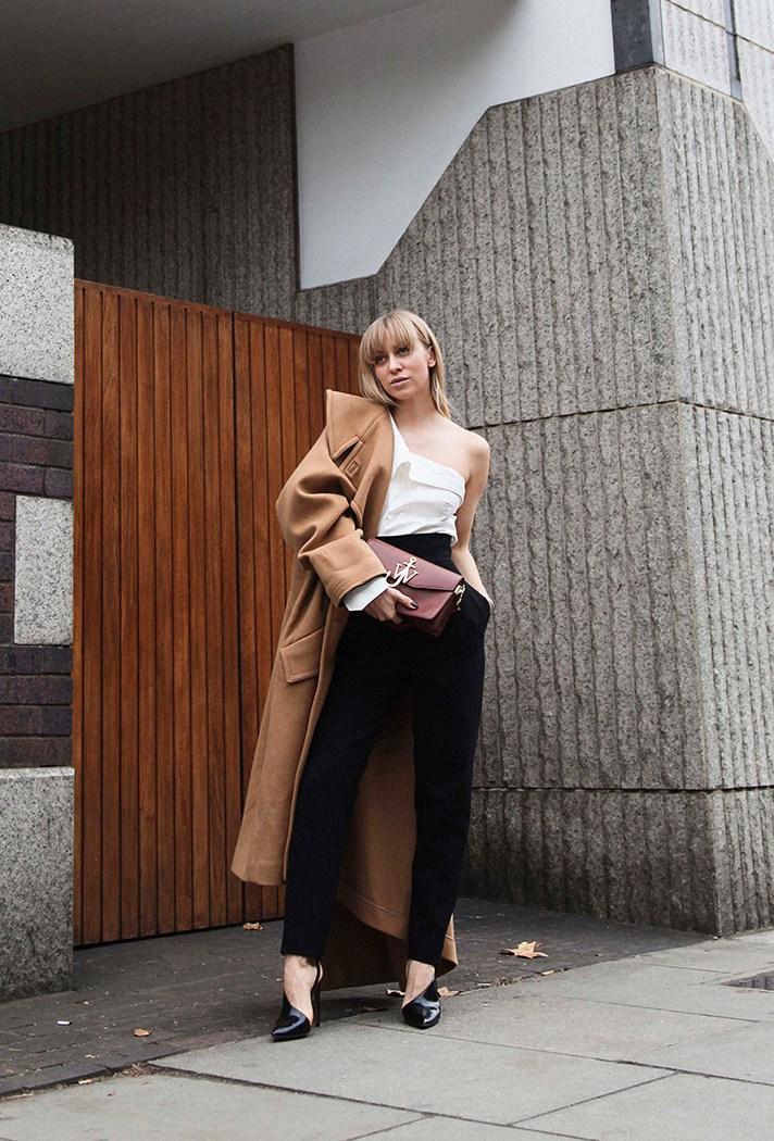Черного цвета брюки в сочетании с праздничной белой блузкой и светло коричневым пальто.