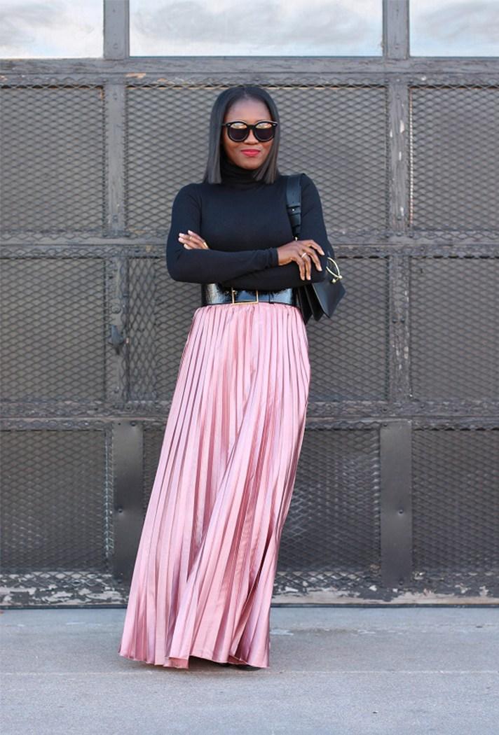 Розовая блестящая гофрированная юбка в пол с черной водолазкой.