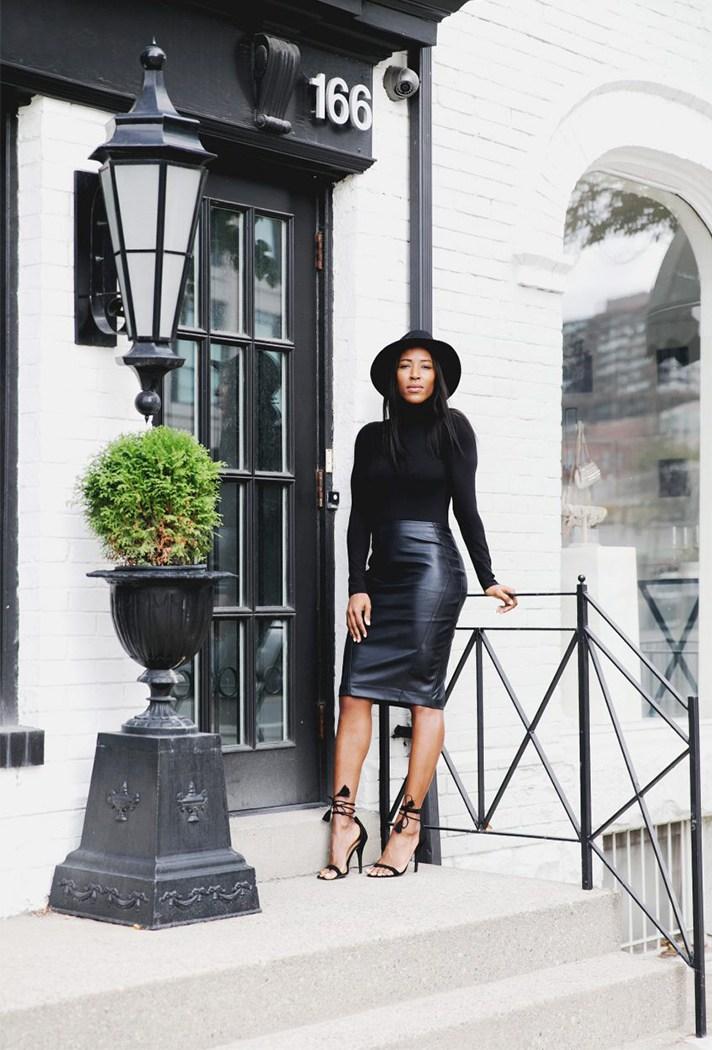 Черного цвета блестящая юбка св сочетании с черным свитером.