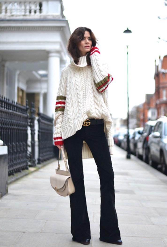 Черного цвета брюки с сочетании с белым вязаным оьемным свитером.
