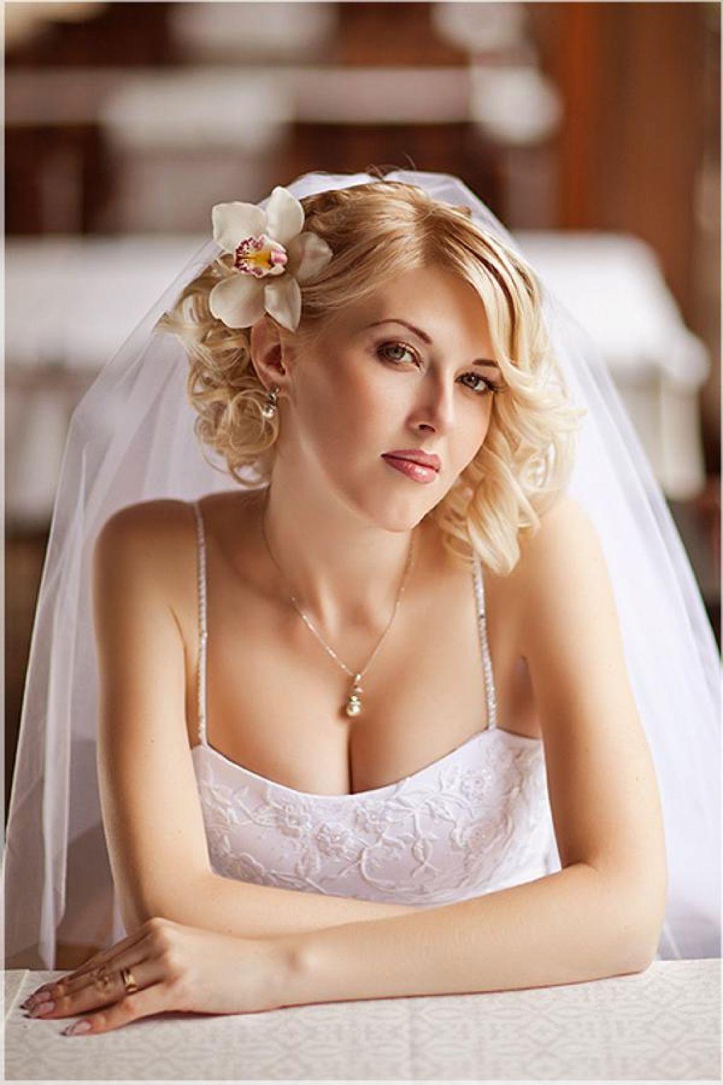 свадебная короткая причёска с фатой и с цветком сбоку в волосах.