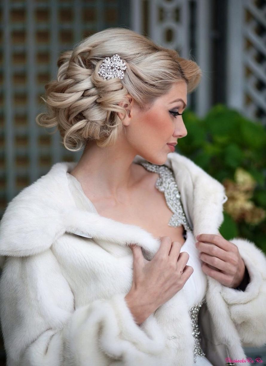 свадебная прическа с крупными локонами с заколкой. в волосах.