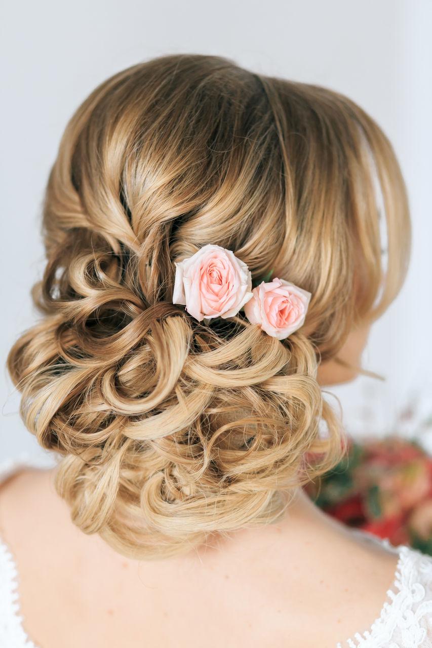свадебная прическа с локонами и украшениями в виде цветов.