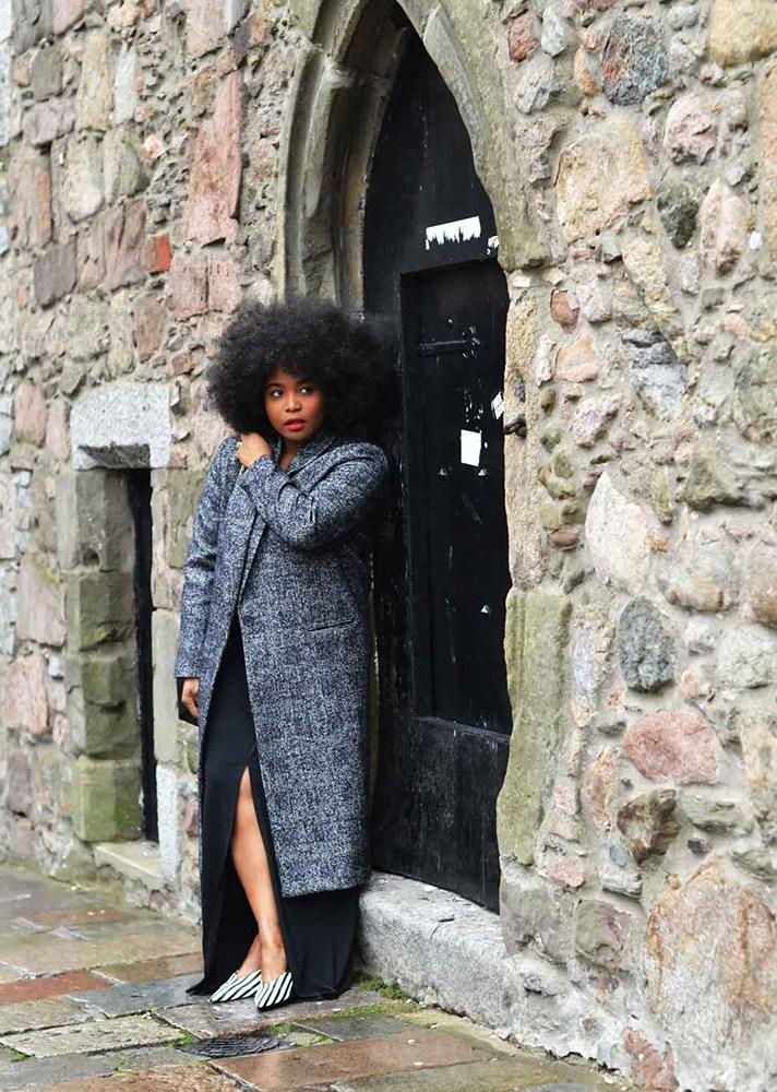 Серое пальто в сочетании с длинной черной юбкой с большим разрезом..