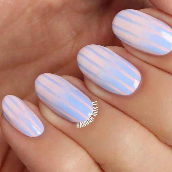 Нежно розовый маникюр с геометрическими голубыми полосками на овальных ногтях средней длины