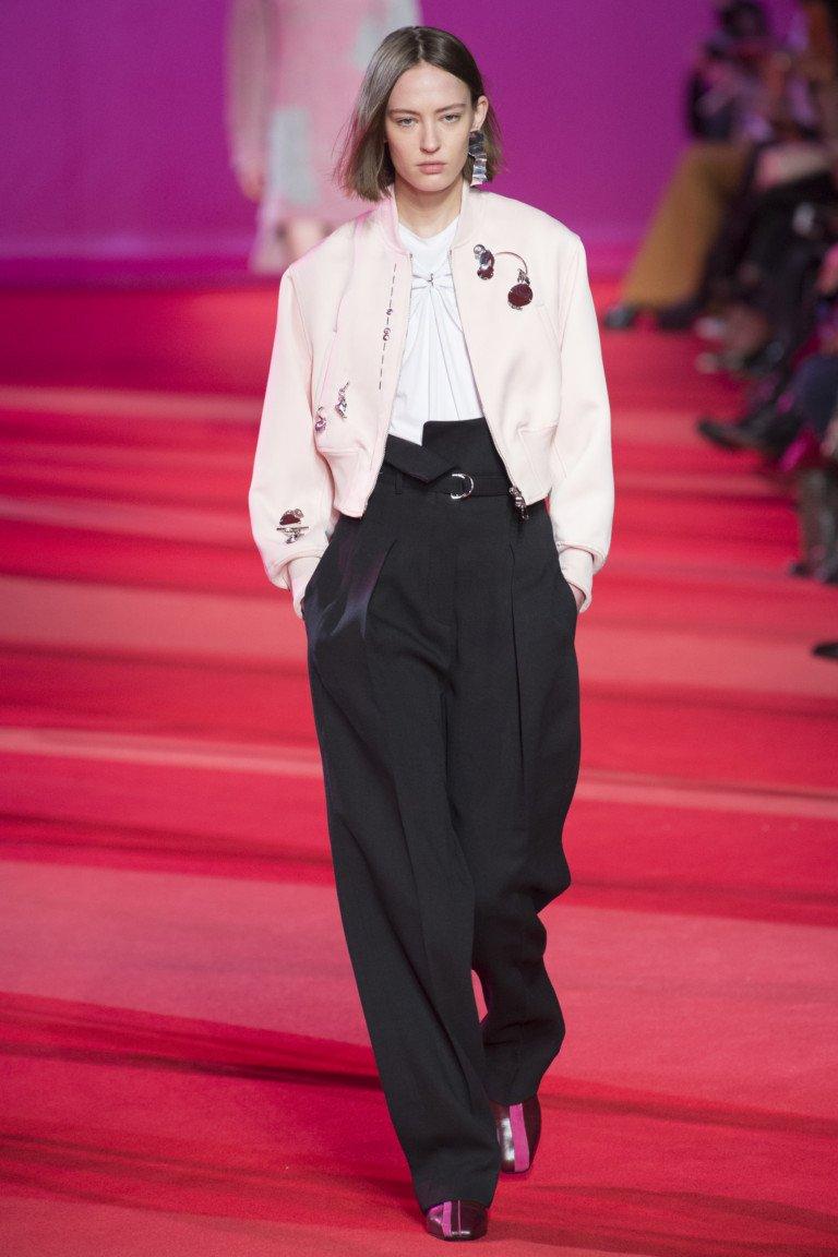 Белая блузка с маленьким пиджаком бледно-розового цвета с черными широкими длинными брюками с высокой талией.