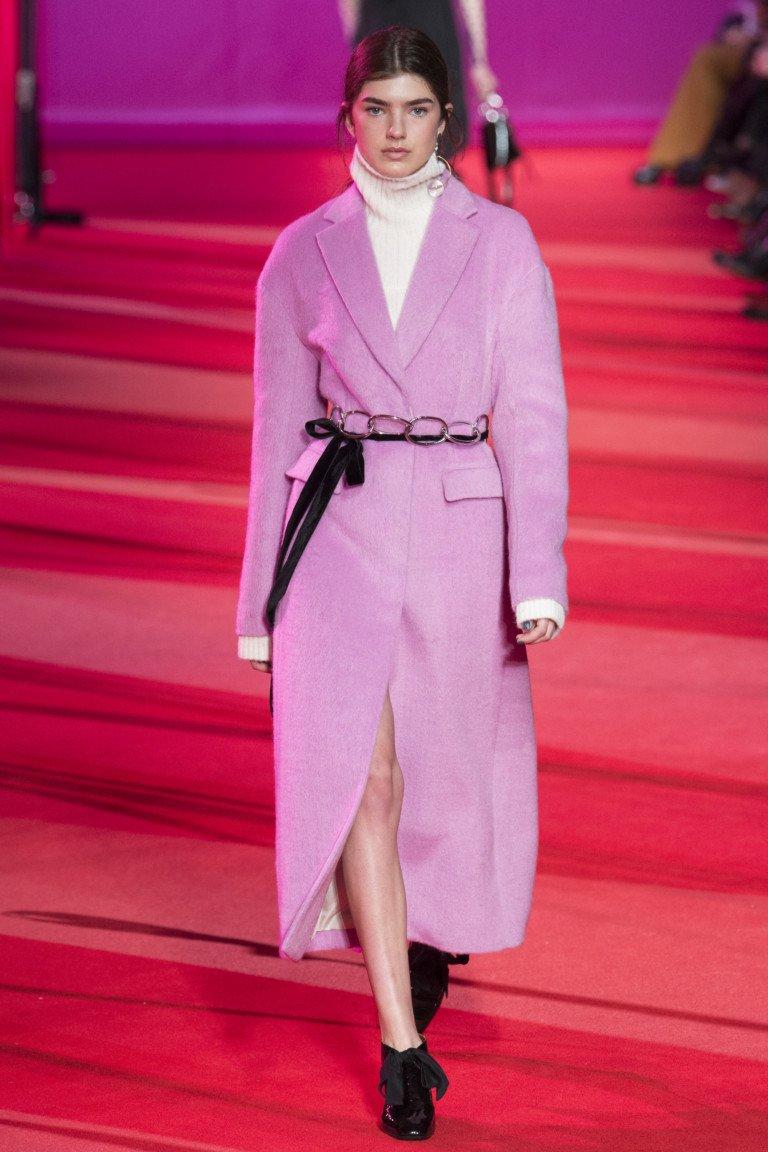 Розово-фиолетовое пальто с тонким черным поясом и черными ботинками.