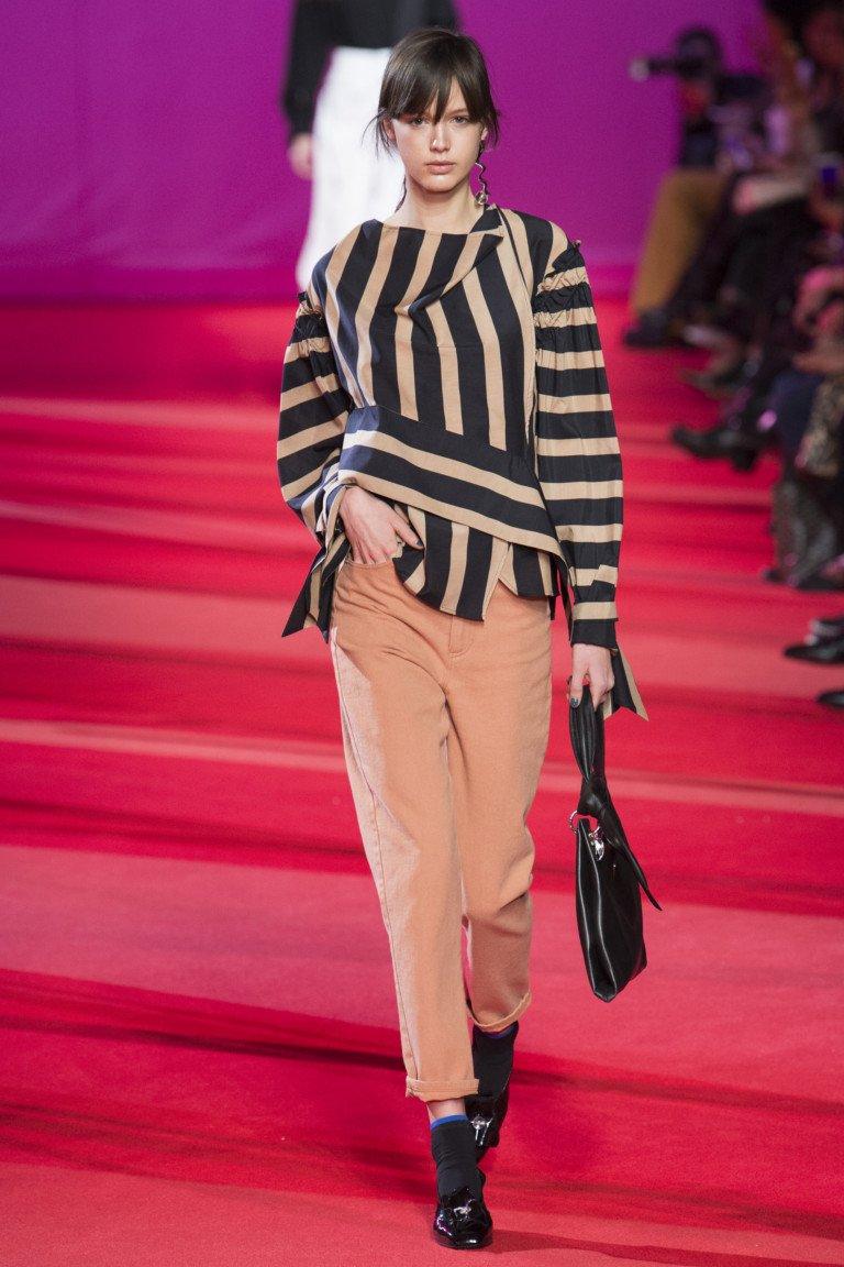 Ассимтричной формы блузка в полоску с укороченными брюками крмового цвета.