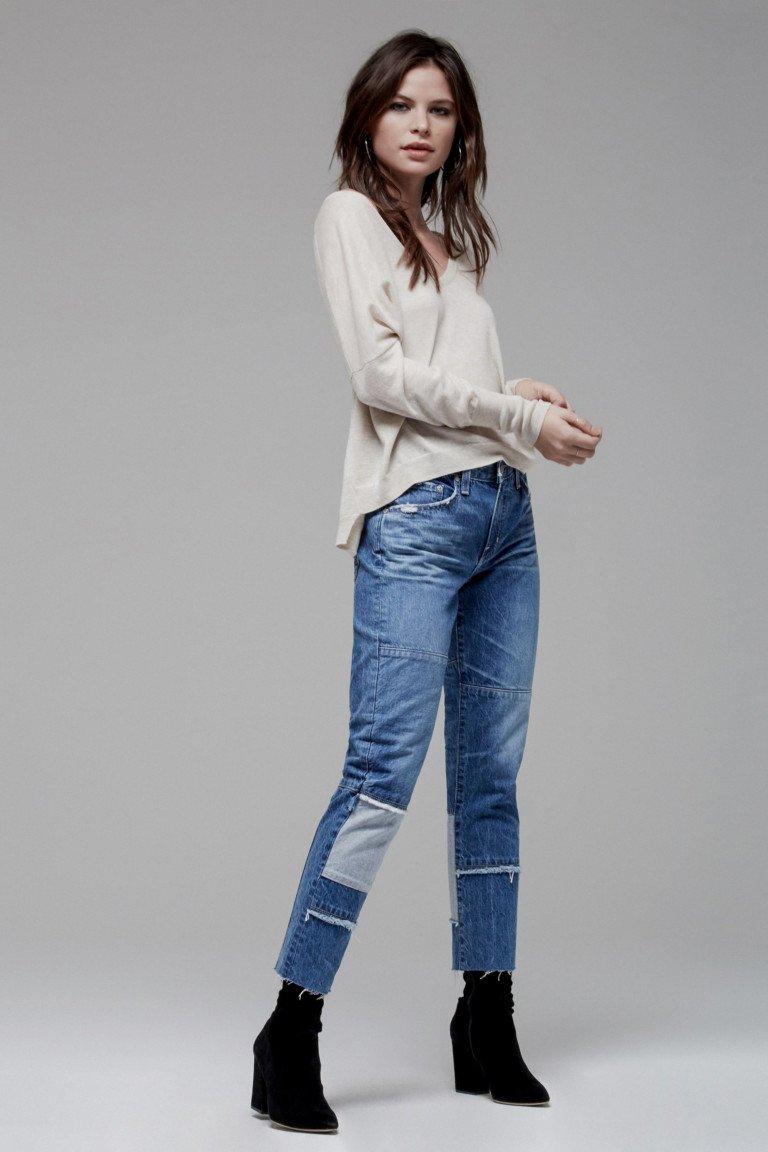 Белая кофта с неподшитыми джинсами и черными короткими сапогами.