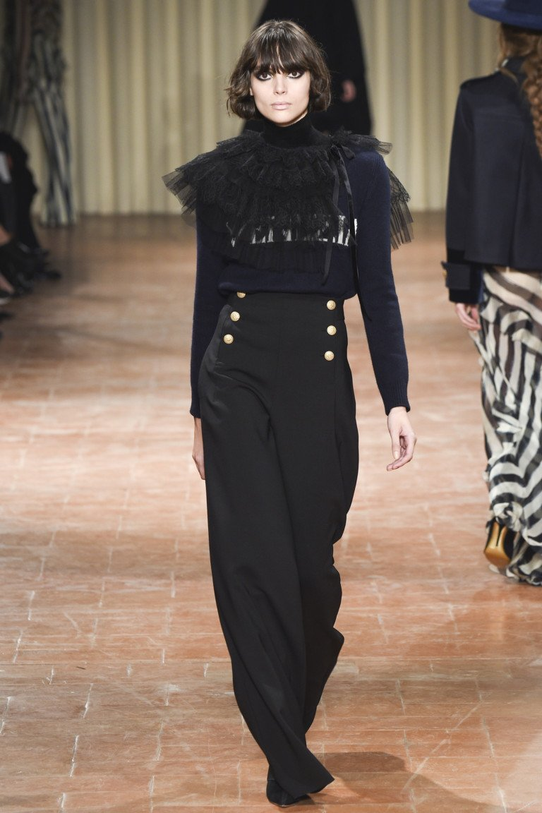 Черные широкие длинные брюки с черной кофтой с кружевным воротником.