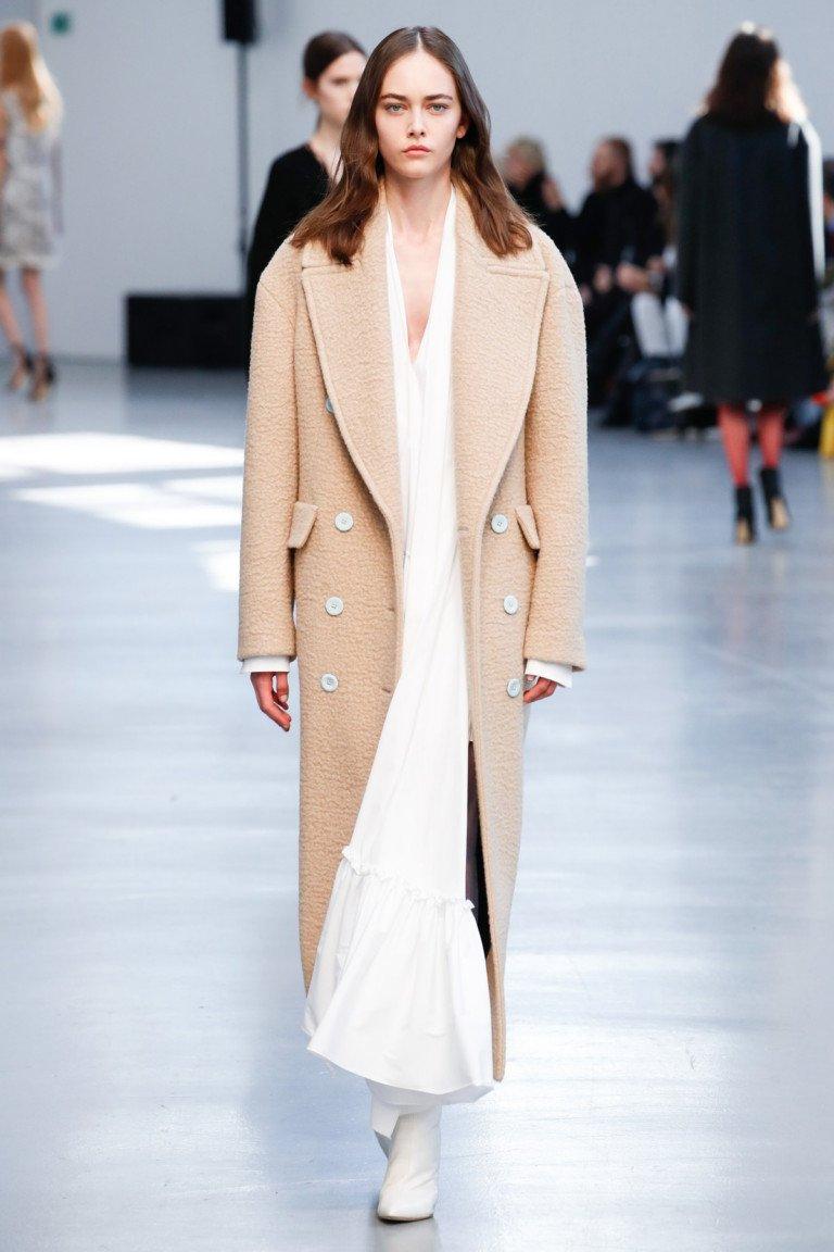 Светло бежевое пальто с большим отложным воротником и белыми сапогами.