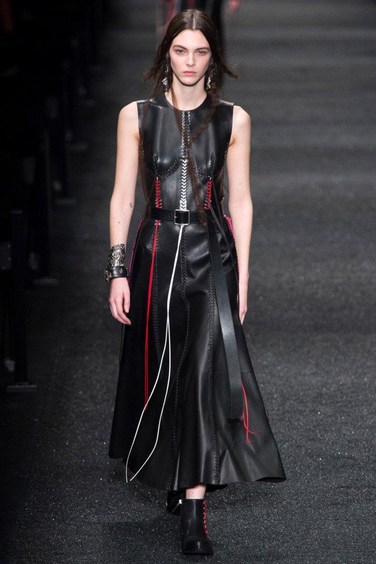 Кожаное черное платье со шнуровкой красного и белого цвета с такого же цвета ботинками.