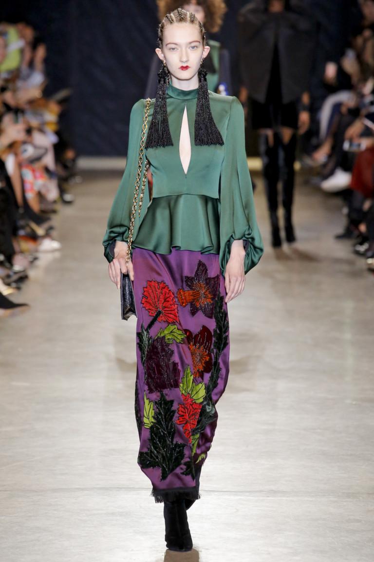 Зеленого цвета атласная блузка с пышными рукавами и ярко-фиолетовая длинная юбка с крупным цветочным принтом.