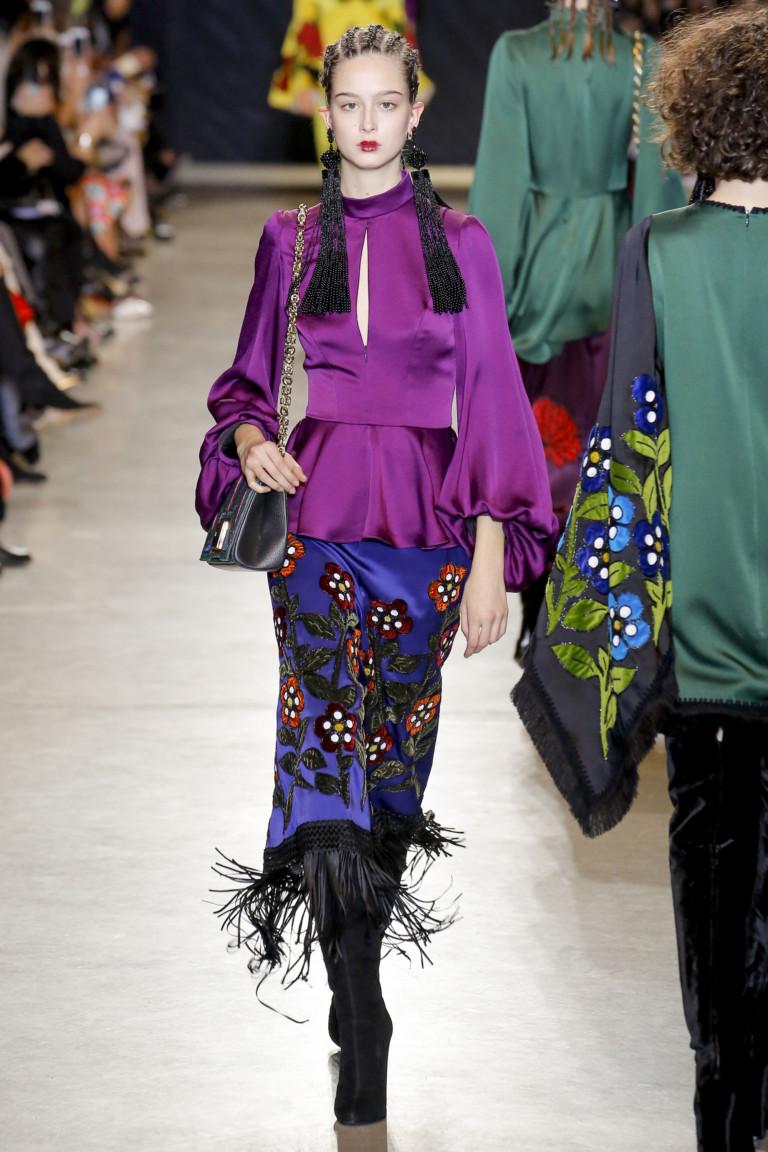 Ярко-фиолетового цвета атласная блузка с пышными рукавами и ярко-синяя атласная юбка с крупным цветочным принтом и черного цвета бахромой.