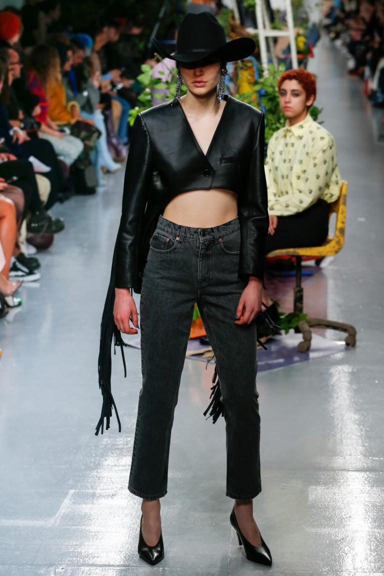 Черная короткая курточка с бахромой и короткими джинсами.