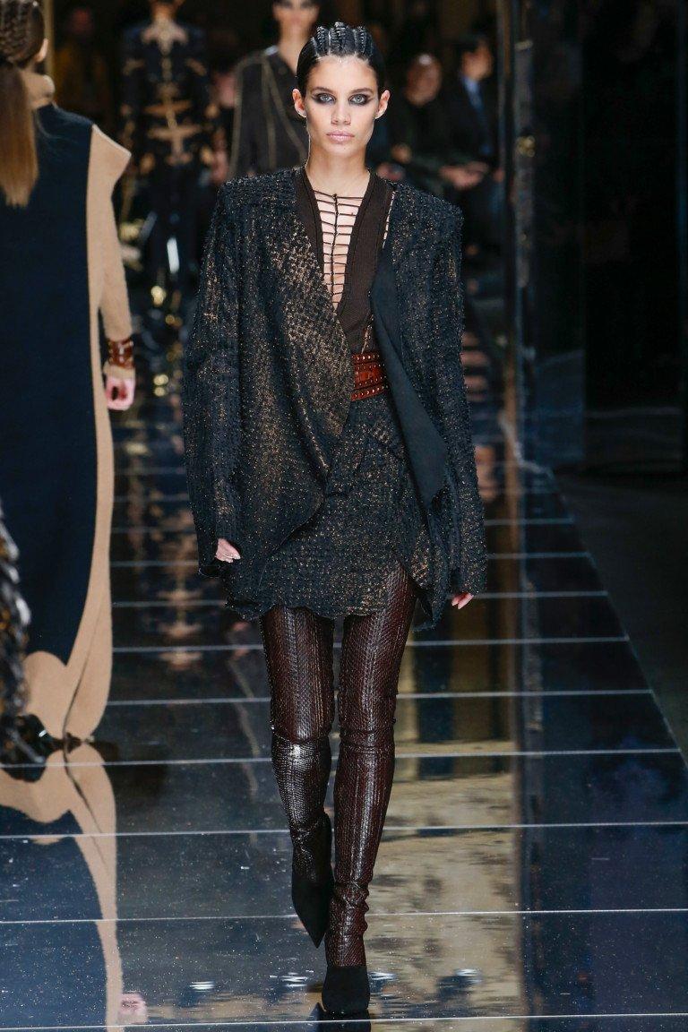 Черного цвета с золотом пиджак с скороткой юбкой и коричнего цвета кожаные лосины.