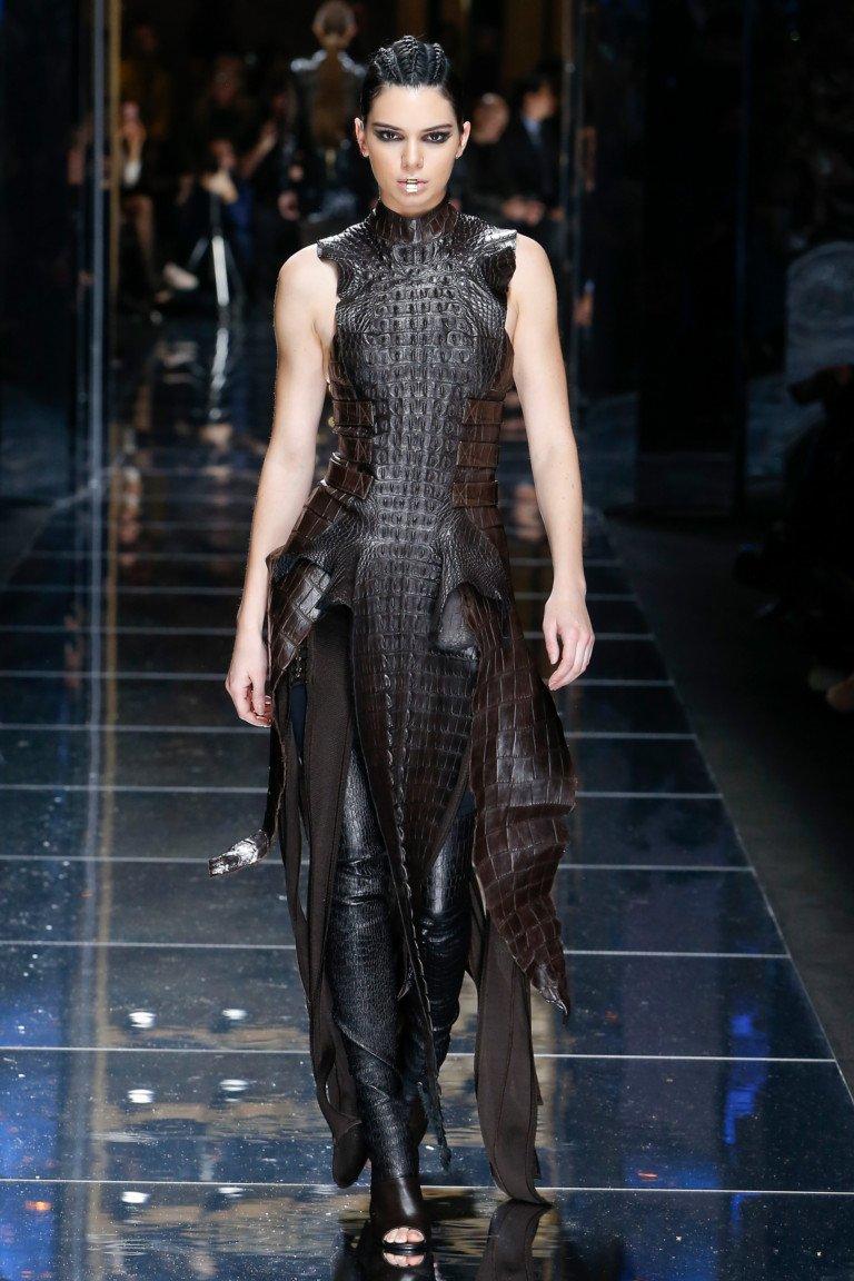Коричневого цвета кожаное платье с большими разрезами и кожаными лосинами.