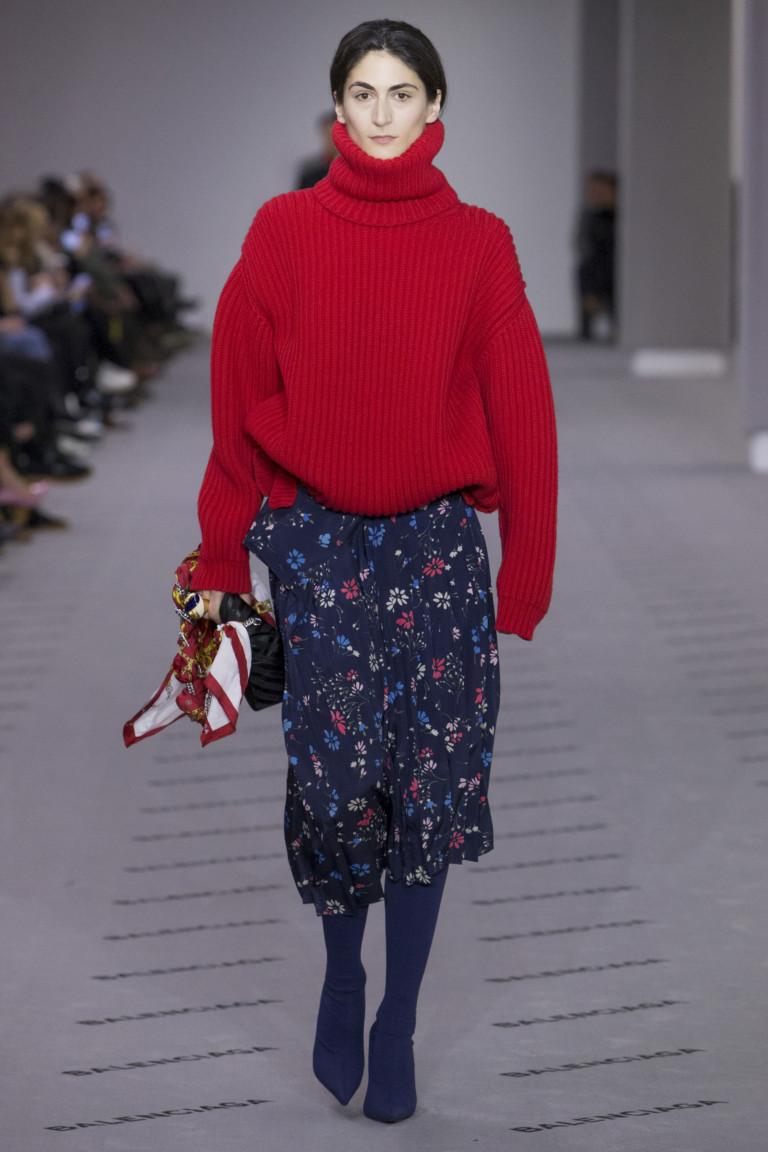 Красный объемный свитер с синей юбкой с цветочным принтом.