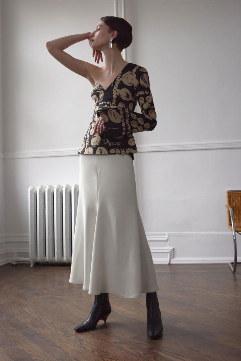 Ассиметричная черная блузка спринтом и одним рукавом и длинной белой расклешенной юбкой.