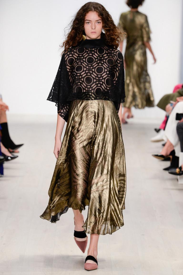Расклешенная юбка золотого цвета с принтом и черная кружевная блузка.