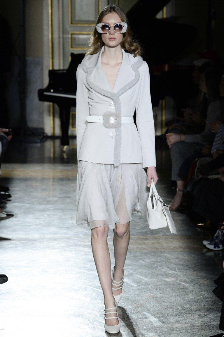 Свело - серый пиджак с меховой опушкой и кожаным ремнем с прозрачной юбкой.