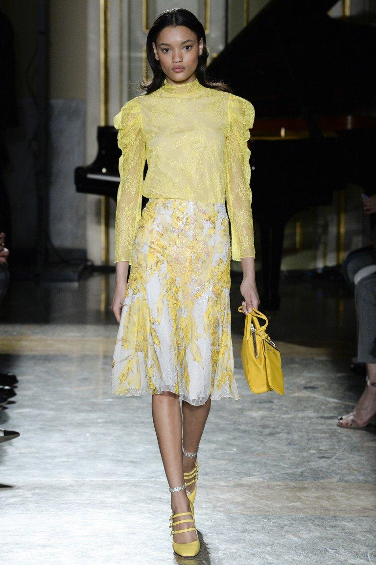 Желтая кружевная блузка с длинными рукавами и кружевная белая юбка в крупный желтый цветочек с желтыми туфлями и сумкой.