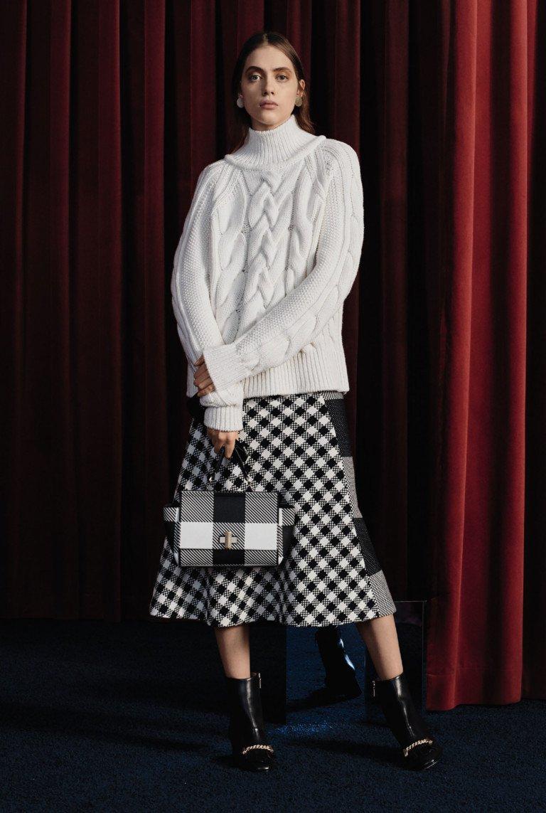 Белый свитер с ажурной вязкой и клетчатая расклешенная юбка.