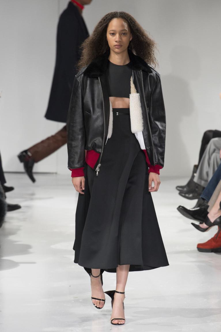 Ченая кожаная куртка бомбер с красной резинкой на рукавах и поясе и черное расклешенное платье.