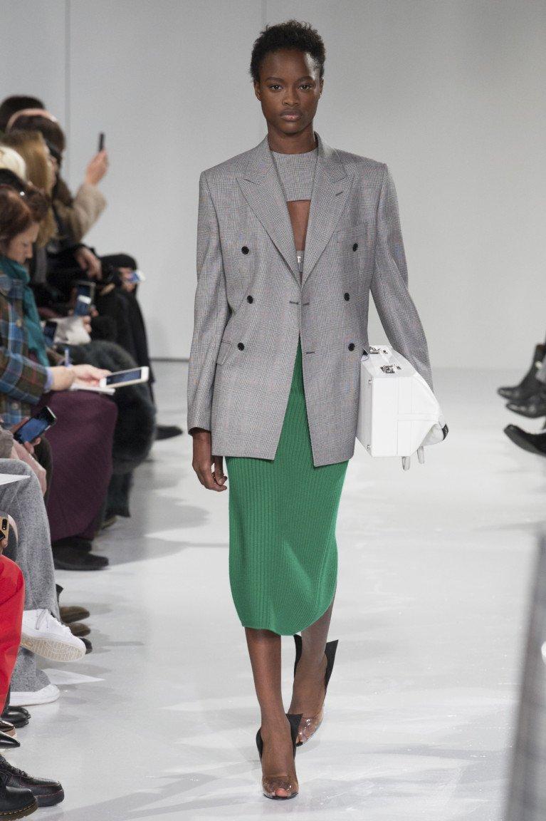 Светло-серый элегантный пиджак с узкой зеленой юбкой.
