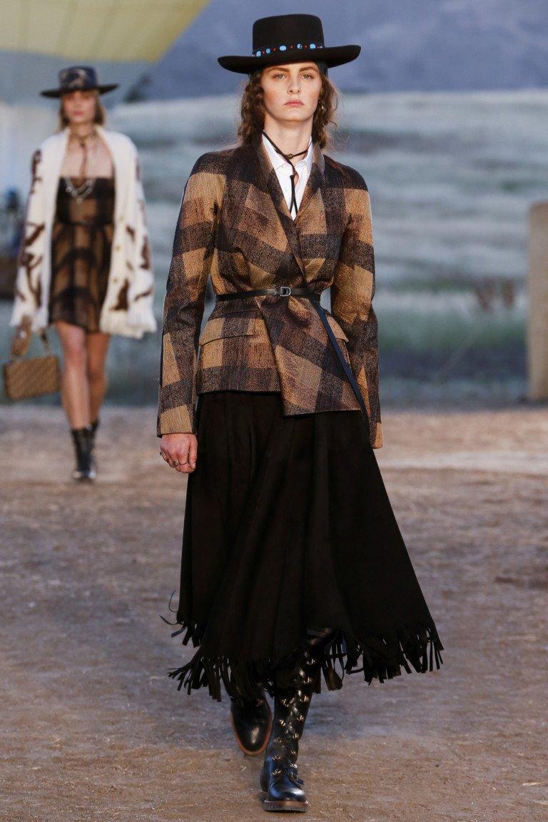 Пиджак в клетку с черной юбкой с бахромой и черной шляпой.